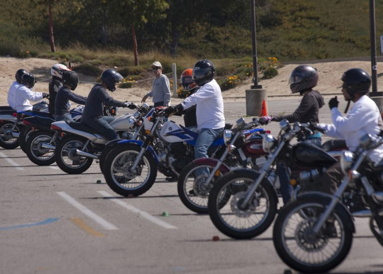 On Saturday, March 10, 2012, Howard Kaplan (center) leads a group of motorcyclists in the north parking lot of College of the Canyons in Santa Clarita, Calif. Kaplan, a retired fire captain, is employed by Nelson Motorcycle Training Center (NMTC), Inc., Las Vegas, Nev. NMTC is a private contractor hired by the California Motor Safety Program (CMSP), the official motorcycle safety and training program for the State of California. The purpose of the program is to provide training for motorcyclists to obtain the proper license endorsement. The course requires participants to complete 10 hours of practical and 5 hours of class participation. Kaplan says that there are many riders that do not have a motorcycle endorsement on their driver's license. (Photographed by Jan C. Bernard)
