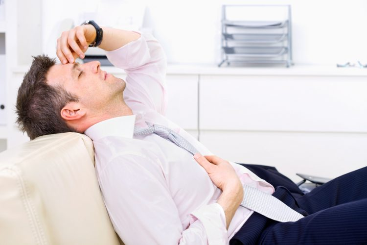Mid-adult businessman lying on couch at office, looking exhausted eyes closed. Bright background. Click here for more business photos: